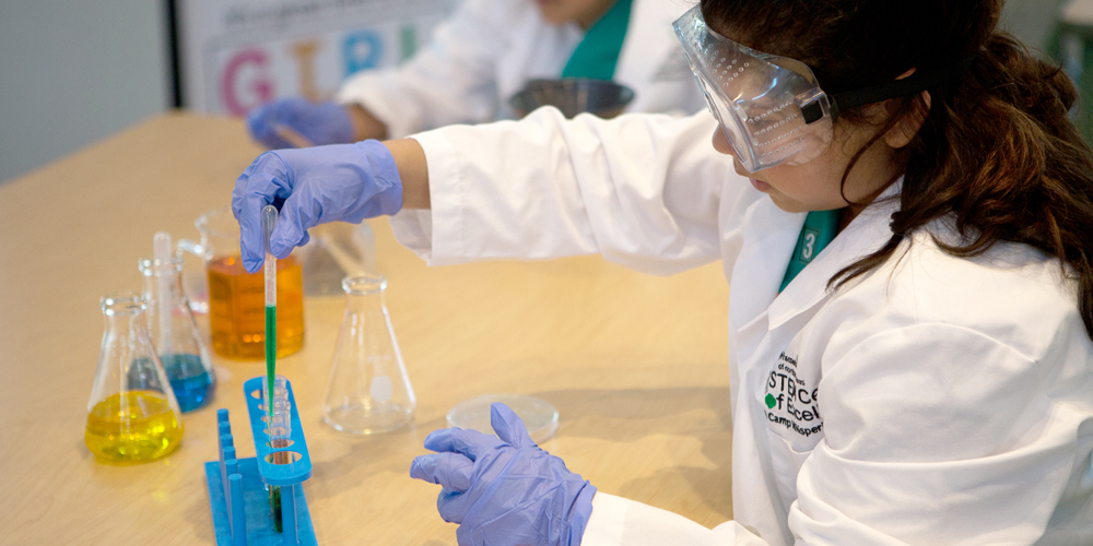 A Girl Scout carefully mixes chemicals at the STEM Center.